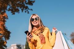 Spadku parka spaceru toreb na zakupy smartphone gawędzenie obraz royalty free