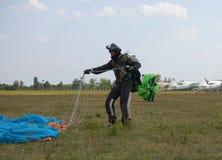 Spadochroniarzów stojaki po lądować na polu w przekładni i odpinają spadochron fotografia stock