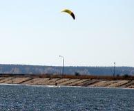 Spadochrony od kitesurfing unoszą się nad wodną ` s krawędzią przeciw jasnemu niebieskiemu niebu fotografia royalty free