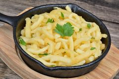 Spaetzle with butter and parsley in a iron pan of bamboo cutting board Stock Images