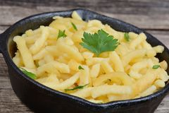 Spaetzle with butter and parsley in a iron pan Stock Photos