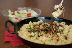 Spaetzle mit geschmolzenem Käse im pan- käsespätzle kasnocken Lizenzfreies Stockbild