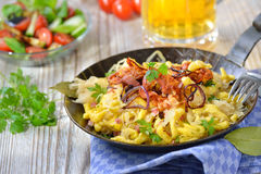 Spaetzle with sauerkraut. Swabian spaetzle with sauerkraut, fried bacon and onion rings on a wooden table with a Munich beer and a side salad Royalty Free Stock Photography