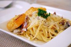 Spagetti Carbonara med bacon tjänade som med den stora krutongen, det är frasigt och kryddat bröd som förlades på maträtt för vit royaltyfri bild