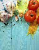 Spagetti för matpreparatio för olja sund matställe, vegetarisk svartpeppar för ultrarapidvitlöktomat på en träblått Royaltyfri Foto