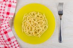 Spagetti i platta, rutig servett och gaffel på trätabellen Arkivfoton