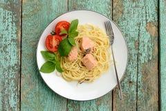 Spagetti med basilika, tomater och laxen på turkos sjaskig ta Royaltyfri Bild
