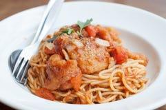 Spagetti med den kryddiga stekte fisken på sås Royaltyfria Bilder