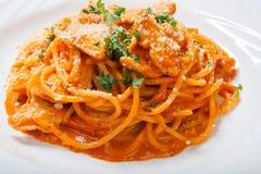 Spagetti med höna som lagas mat i kryddig sås från tomater, löken och vitlök royaltyfria bilder