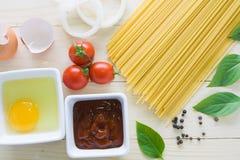 Spagetti med ingredienser för att laga mat på wood bakgrund Arkivfoto