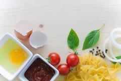 Spagetti med ingredienser för att laga mat på wood bakgrund Royaltyfri Bild