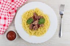 Spagetti med kalopets i plattan, ketchup, servett, gaffel arkivbild
