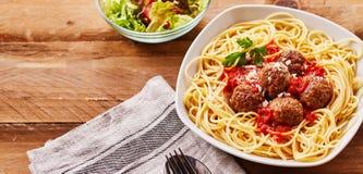 Spagetti och köttbullar som tjänas som med sidosallad arkivbild