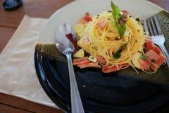 Spagetti och skinka på den keramiska plattan Arkivbild