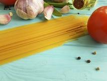 Spagetti olja i en flaska, vitlök, tomat, svartpeppar på en blå träbakgrund Royaltyfri Fotografi