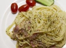 Spagetti på en vit platta med nya tomater och gurkor Royaltyfri Fotografi