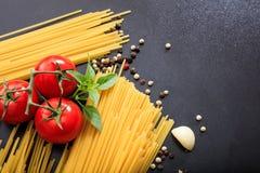 Spagetti, tomater och vitlök på svart bakgrund Royaltyfri Bild