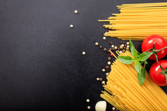 Spagetti, tomatoes and garlic on black background. Spagetti pasta, tomatoes and garlic on black background Royalty Free Stock Image