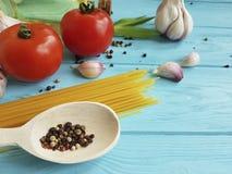Spagetti torkad tomatvitlök som lagar mat italiensk förberedelsepeppar, olje- näring en blå träbakgrund Arkivbilder