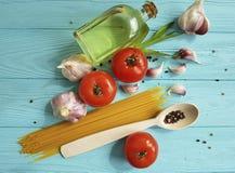 Spagetti torkad tomatvitlök som lagar mat italiensk peppar, olje- näring en blå träbakgrund Arkivbilder