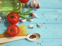 Spagetti torkad tomatvitlök som lagar mat peppar, olje- näring en blå träbakgrund Royaltyfri Fotografi