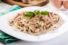 Spagetticarbonara med bacon och basilika Arkivfoton