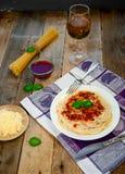 Spagettipasta med tomatsås, Chees och basilika med exponeringsglas för vitt vin på trätabellen traditionell matitalienare royaltyfria bilder