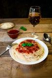 Spagettipasta med tomatsås, Chees och basilika med exponeringsglas för vitt vin på trätabellen traditionell matitalienare royaltyfri fotografi