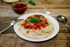 Spagettipasta med tomatsås, ost och basilika på trätabellen traditionell matitalienare royaltyfri fotografi