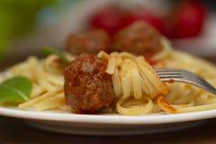 Spagettipastaköttbullar med tomatsås, basilika, örtparmesanost på träbakgrund arkivbilder