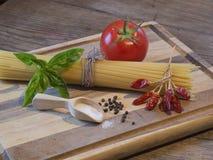 Spagettipeperoniingrediens på den röda träskärbrädan och royaltyfri foto