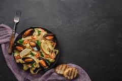 Spagettivongole, italiensk havs- pasta med musslor och musslor, i platta med örter och exponeringsglas av vitt vin på den lantlig arkivbild