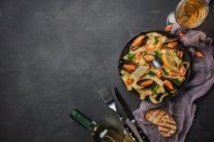 Spagettivongole, italiensk havs- pasta med musslor och musslor, i platta med örter och exponeringsglas av vitt vin på den lantlig fotografering för bildbyråer