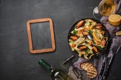 Spagettivongole, italiensk havs- pasta med musslor och musslor, i platta med örter och exponeringsglas av vitt vin på den lantlig arkivfoton