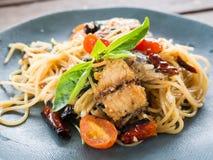 Spaghetti épicés asiatiques avec le maquereau, le basilic et frais sec dans le plat en céramique Photo libre de droits