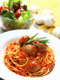 Spaghetti. A plate of beef meat balls spaghetti with a bowl of salad and some garlic as background stock image