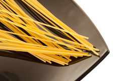 Spaghetti. Uncooked spaghetti on a black plate isolated Stock Images