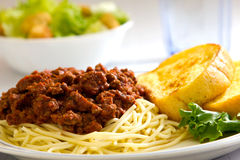 Spaghetti. With garlic bread sitting next to it with a salad and a glass of water in the background Royalty Free Stock Photo