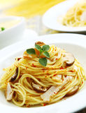 Spaghetti Aglio Olio. A plate of aglio olio spaghetti with mushroom and chicken meat garnishing royalty free stock photography
