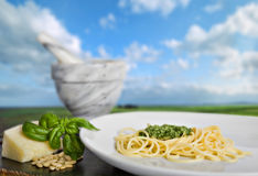 Spaghetti al pesto. (a tipical italian basil's sauce), in front of a beautiful italian landscape Royalty Free Stock Photo