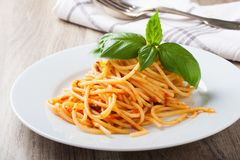 Spaghetti al pomodoro. One of the simplest Italian rustic dishes with the pasta tossed in a sauce of tomato, basil, garlic and a little sugar and oil Stock Images