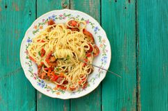 Spaghetti al Pomodoro in white plate with fork on wooden turquoi. Se table top view above view Royalty Free Stock Image