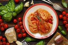 Spaghetti alla amatriciana. On a wooden table top view royalty free stock photography