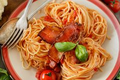 Spaghetti alla amatriciana. On a wooden table top view stock photos