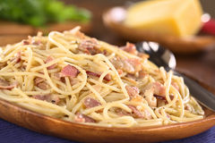 Spaghetti alla Carbonara. Spaghetti (Pasta) alla Carbonara with bacon, cheese, egg, cream on rustic wooden plate with parmesan cheese in the back (Selective Royalty Free Stock Images