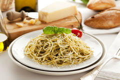 Spaghetti alla Genovese dish on table. Spaghetti with Genovese pesto sauce, garnished with basil leaf and tomato, parmesan cheese and bread in background Royalty Free Stock Photo