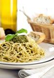 Spaghetti alla Genovese dish on table close up. Spaghetti with Genovese pesto sauce, wine and ciabatta bread in background Stock Image