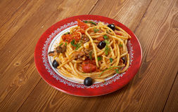 Spaghetti alla puttanesca. Salty Italian pasta dish.ingredients are typical of Southern Italian cuisine: tomatoes, olive oil, olives, capers and garlic stock photos
