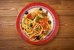 Spaghetti alla puttanesca. Salty Italian pasta dish.ingredients are typical of Southern Italian cuisine: tomatoes, olive oil, olives, capers and garlic royalty free stock photo
