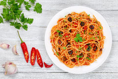 Spaghetti alla puttanesca with capers, top view. Delicious Spaghetti alla puttanesca with capers, olives, anchovies, tomato sauce sprinkled with parsley on white royalty free stock photos